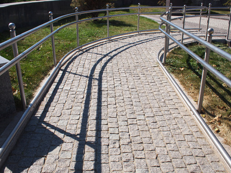 wheelchair access: Ramp for physically challenged from the granite pavement on a sunny summer day with midday shadows