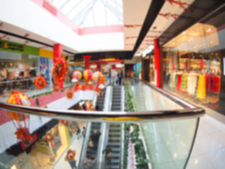 view of a staircase in a shop: Blurred top view on escalator in the shopping mall with wide angle distortion view. Image was defocused for use as background Stock Photo