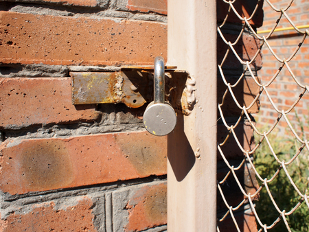 keep gate closed: Detail of the gate of the metal mesh that are closed to the padlock and a fragment of a brick wall closeup Stock Photo