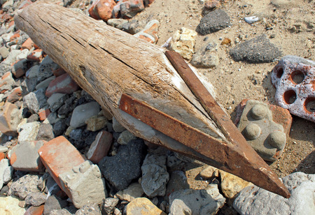 tip up: Wooden pole with an iron tip at a construction site. Selective focus close up.