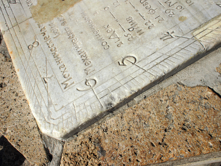 coquina: Detail of old sundial clock face closeup. On a marble slab engraved with numbers and names of the months in Russian.
