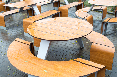 dank: Wet round outdoor cafe tables on the street after a rain fall on the wet pavement with a few yellow fallen leaves.