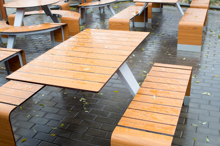 dank: Wet outdoor cafe tables on the street after a rain fall on the wet pavement with a few yellow fallen leaves. Selective focus. Stock Photo