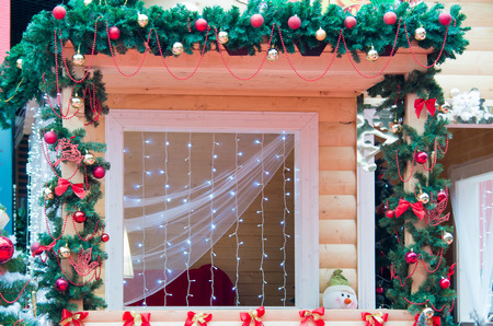 finery: Window decorated in Christmas style Christmas garlands, ribbons, bows, Christmas balls and fir branches
