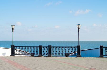 seafront: View of the embankment of the lake with lanterns lighting, stone pavement and a metal fence before descending to the beach against a blue sky with clouds.