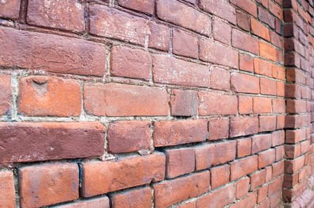 distal: Selective focus on a brick wall at an angle with a diffuse distal portion to be used as background