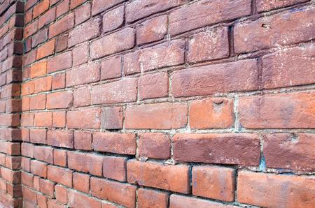 enfoque selectivo en la pared de ladrillo rojo en un ángulo con una parte distal difusa que se utilizará como fondo