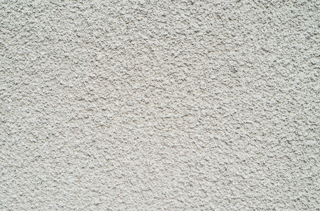 parget: Detail of gray wall closeup uneven granular cement coating for use as a background