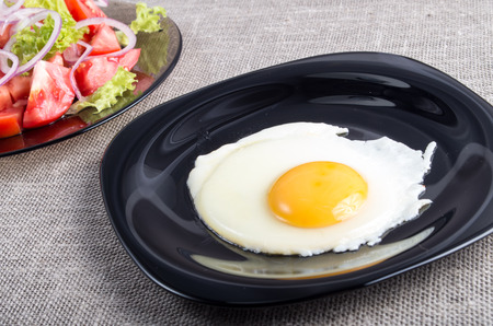 Useful homemade breakfast of fried egg and a salad of chopped tomato on a plate on tabletop Stock Photo