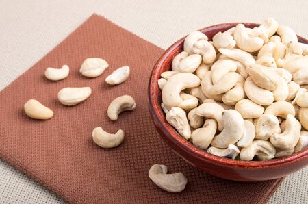 Close Up view on raw cashew nuts for vegetarian food in a wooden cup on a fabric tablecloth. Selective focus.
