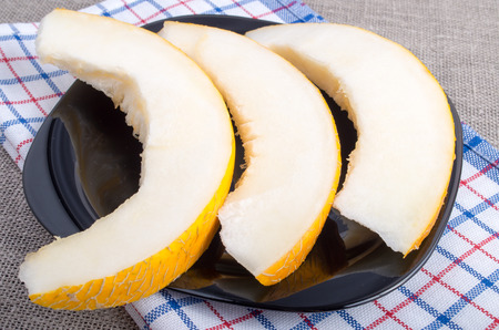 useful: Healthy and useful dessert of sweet yellow melon slices on a black plate on tablecloth background Stock Photo