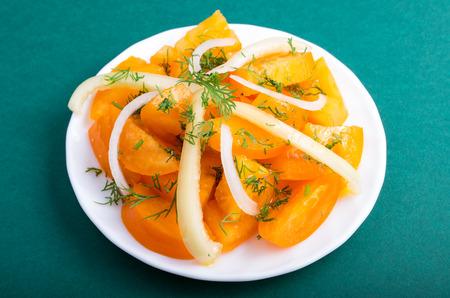 finocchio: Insalata dei pomodori e delle cipolle arancio crudi su un primo piano verde del fondo