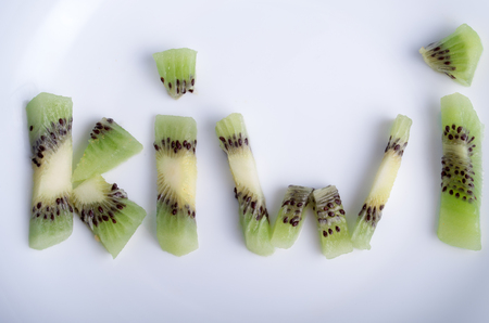 kiwi fruta: Top view of the word kiwi, letters made up of pieces of kiwi fruit on an empty white plate closeup Foto de archivo