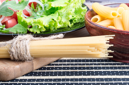 detail of bunch: Detail of table with natural food closeup - fresh green salad, pasta in a wooden bowl and a bunch of spaghetti on a wooden board Stock Photo
