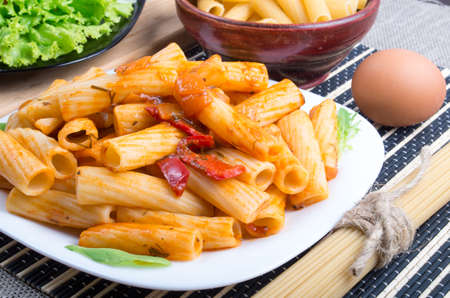 View closeup on a dish of rigatoni pasta with vegetable sauce next to the plate with lettuce and ingredients for cooking Stock Photo