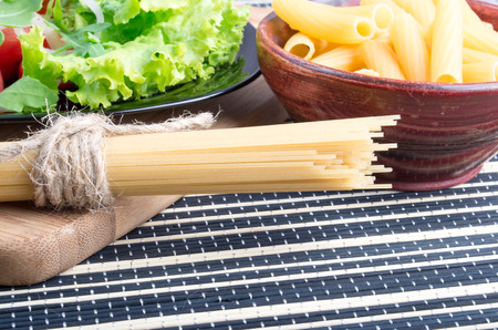 detail of bunch: Detail of table with food closeup - lettuce in a black plate, pasta in a wooden bowl and a bunch of spaghetti on a wooden board
