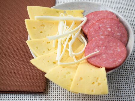morsel: Plate with snacks on the table - slices of salami, cheese and sheep cheese pieces closeup with shallow depth of focus. Stock Photo