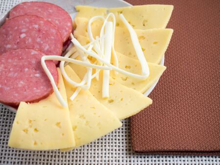 morsel: Plate with snacks on the table - slices of salami, cheese and sheep cheese slices closeup