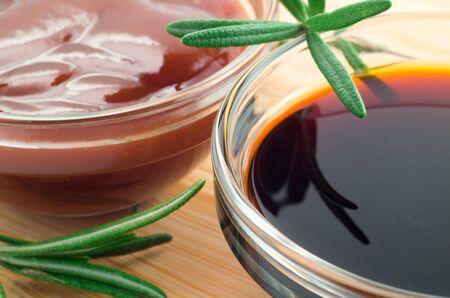 Ketchup aux tomates et sauce soja dans un bol transparent orné de brins de romarin sur une table en bois à faible profondeur de champ
