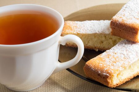 bisquit: White cup of tea and a plate with slices of sweet cake with powdered sugar closeup Stock Photo