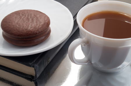 chocolate biscuit: White cup with cocoa and chocolate covered biscuit near the old book with reflection on the shiny surface of the table. Stock Photo