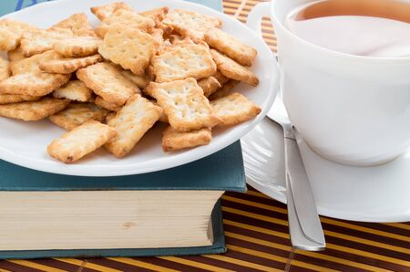 View close-up on a cup of tea and dry crackers on an old book Stock Photo