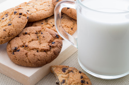 Transparent cup with milk and oatmeal cookies with chocolate close-up on wooden tray with shallow depth of focus Stock Photo