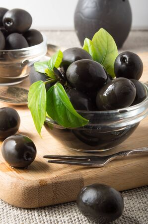 Black olives in a glass bowl decorated with green leaves on the old vintage tablecloths and fork with a small depth of focus