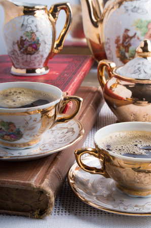 Vintage coffee break. Antique porcelain coffee cups with hot coffee and crockery for breakfast