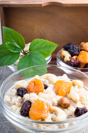One serving of oatmeal with fruit in a glass bowl for breakfast with a blurred background