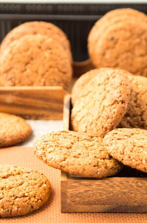 Many of oatmeal cookies in two wooden boxes on a brown fabric blur and shallow depth of field