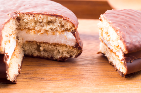 Macro view of the chocolate chip cookies with a layer of milk souffle on a wooden surface close-up with shallow depth of focus Stock Photo