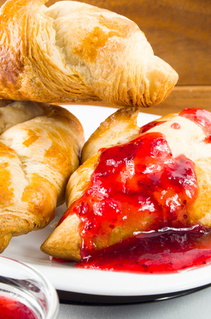 Several croissants smeared with strawberry jam on white plate closeup