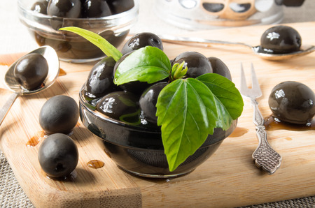 Black olives on a table and glass cups with oil decorated with green leaves on a wooden tray and vintage crockery with shallow depth of focus