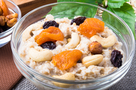 View close-up on a portion of oatmeal with fruit, cashew nuts and berries in a glass bowl for breakfast on a gray tablecloth Stock Photo