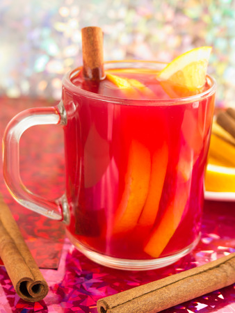 Glass mug with citrus mulled wine, cinnamon and orange to bright shiny background with blur and shallow depth of focus Stock Photo