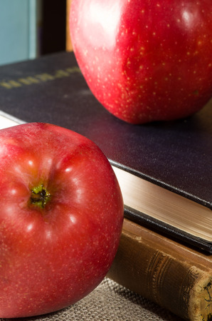 Fragment of old books with hardcover and close-up red apples on old gray tablecloths with shallow depth of field