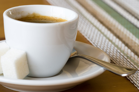 Small cup of espresso on a saucer with sugar close-up with shallow depth of field and selective focus