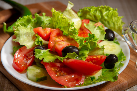 Fresh salad of tomatoes, olives and cucumbers poured with olive oil