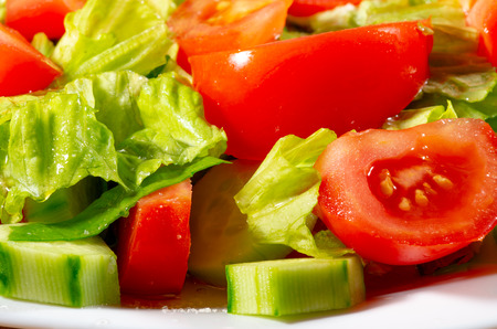 Vegetable mix of fresh cucumber slices, tomatoes, spinach and lettuce close-up with blur.