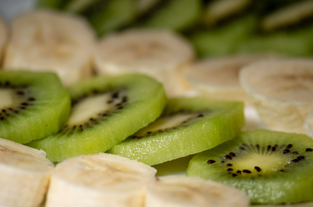 Pieces of kiwi and banana on a plate close-up with shallow depth of field