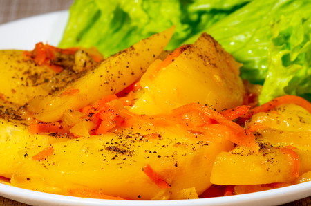 Fragment of a cooked dish of stewed potatoes with pepper and carrots close-up with a blur Stock Photo