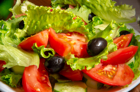 Tasty fresh salad of tomatoes, olives and cucumbers with olive oil