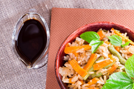 Top view of a dish of rice, carrots and beans with herbs and soy sauce