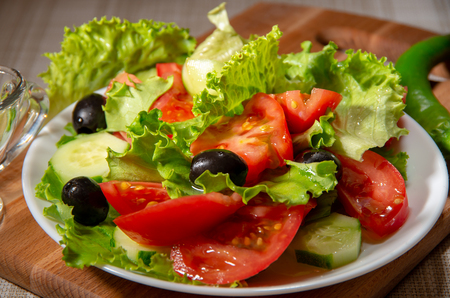 Dish with fresh salad of tomatoes, olives and cucumbers poured with olive oil Stock Photo