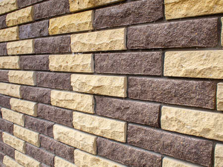 Background from the near view on the wall of bricks of yellow and brown with a blur Stock Photo