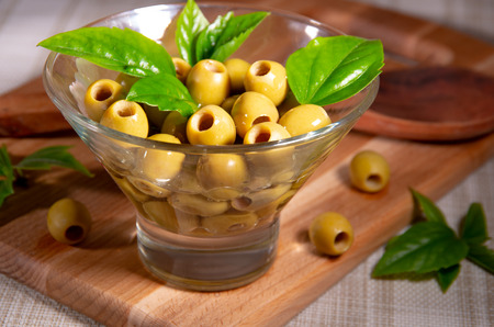 Pitted green olives in a glass cup with olive oil