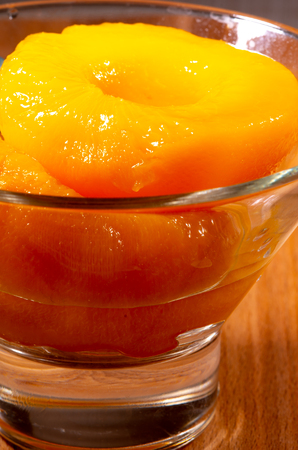 Glass with sweet canned peaches close-up with blur