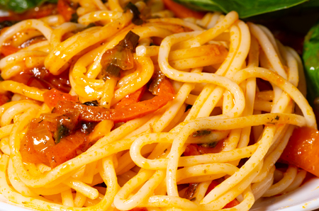 large-scale fragment of a dish of spaghetti and sauce from stewed vegetables with blur and shallow depth of field Stock Photo
