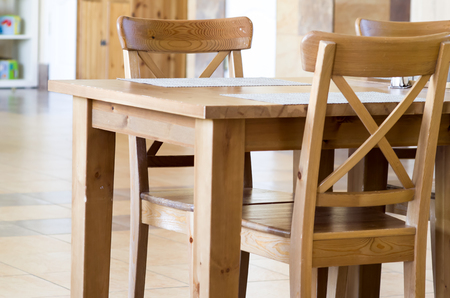 Empty wooden chairs and tables in a cafe with a blurred background and shallow depth of field